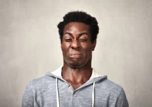 Black man disgust face expressions portrait over gray background.