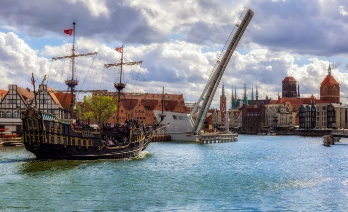 The classic view of Gdansk Old Town with the Hanseatic-style buildings and tourist sailing ship transports tourists across the River Motlawa to the Baltic Sea for a cruise, Poland